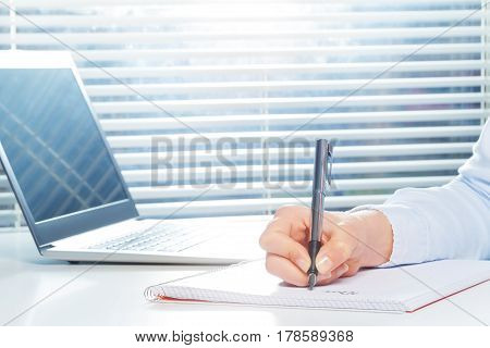 Woman's hand writing on ring-bound notebook with fountain pen next to the laptop at the table
