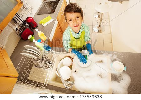 Little boy washing dishes in the kitchen sink with soap view from above
