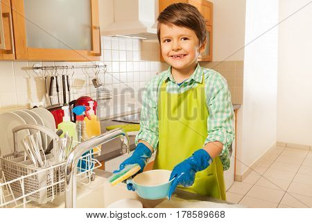 Lifestyle portrait of a boy washing dishes in the kitchen sink smiling to camera and holding mop with soap