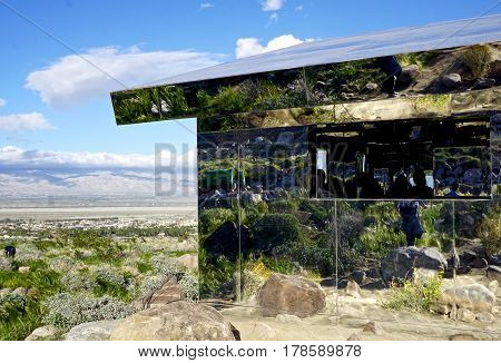 mirrored house in middle of desert landscape
