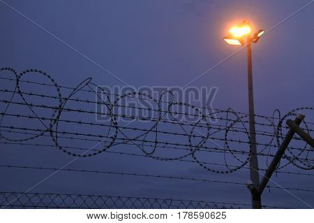 Fence with barbed wire of restricted area at night. Security concept