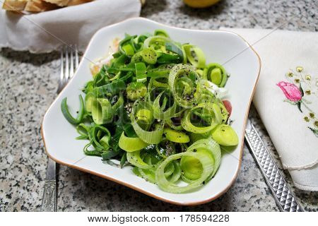 light piquant salad from leek onion under oil and spices