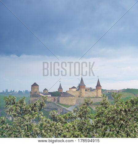 View of the medieval fortress. Tourist attraction, UNESCO World Heritage. Spring landscape with flowering trees. The city of Kamenetz-Podolsky, Ukraine, Europe