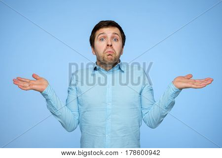 Young Man In Blue Shirt Inflates His Cheeks In Amazement, And Spreads His Hands To The Sides