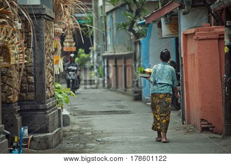 A woman with a meal tray walks down the street of the city of Denpasar Bali