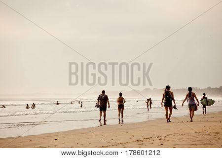 People having a rest on a beach of a city of Kuta island Bali