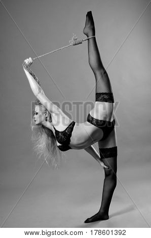 Beautiful blonde Gymnast girl in black stockings, while doing stretching exercises.