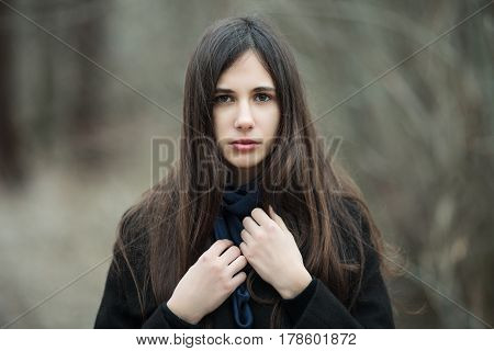 Young Beautiful Girl In A Black Coat Blue Scarf Close Up In Autumn / Spring Forest Park. An Elegant
