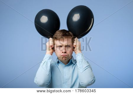 Young Unhappy Man Holding Black Balloons In The Head, Ape. Bad Mood At The Party.