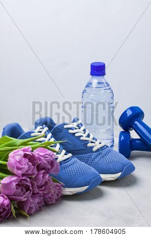 Spring sport composition with blue sneakers dumbbells bottle of water and purple tulips on gray concrete background. Concept healthy lifestyle sport and diet in spring. Place for copyspace.