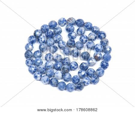 Faceted round beads of blue and white sodalite from Africa isolated on white background