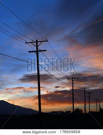 Silhouettes of telephone and power lines and wooden poles stretch across the red, pink and blue skies of a sunset in Alamosa, Colorado during spring
