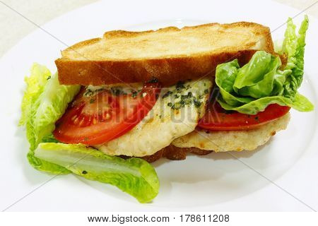 A homemade toasted chicken burger cum sandwich with tomato and lettuce salad