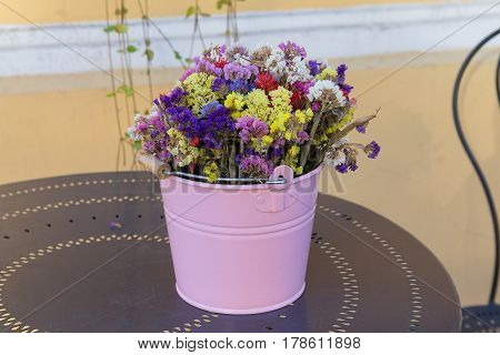 Wildflowers in a colorful bucket on the table