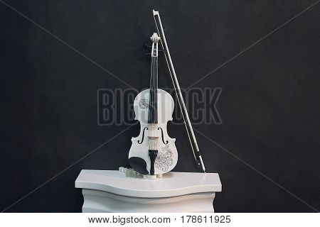 White violin on a pedestal on a black background. Music