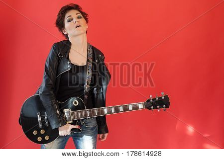 girl with short hair in leather jacket with a guitar