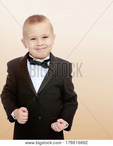 Beautiful little blond boy in a fashionable black suit with a tie.The boy tightly clenched his fists.