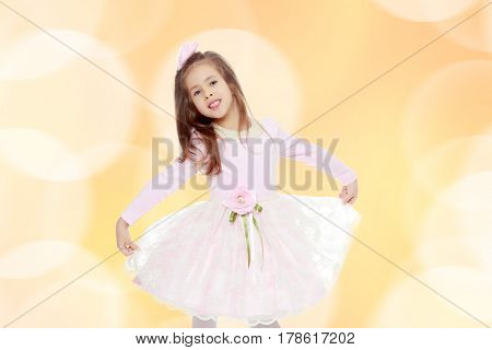 Dressy little girl long blonde hair, beautiful pink dress and a rose in her hair.It stretches over the edges of the dress.Brown festive, Christmas background with white snowflakes, circles.