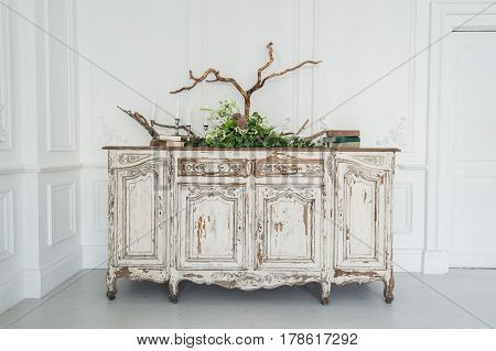 White commode with plants and handmade wool decoration.