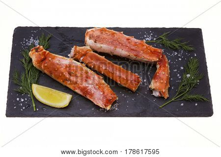 Crab meat with lemon slices and dill on black plate on white background