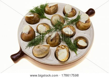 Escargot with butter and spices in a frying pan, a French delicacy of snails