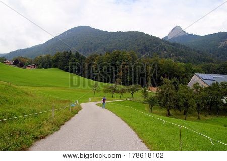 Travel To Sankt-wolfgang, Austria. The Road Between Fields With The Houses And The Mountains On The
