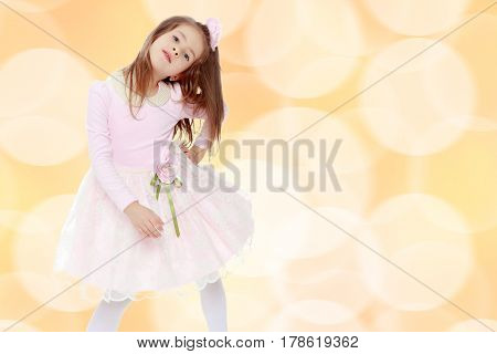 Dressy little girl long blonde hair, beautiful pink dress and a rose in her hair.She put forth a foot.Brown festive, Christmas background with white snowflakes, circles.