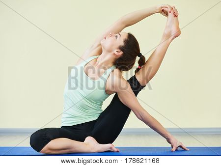 Fitness yoga. Woman doing stretching exercises in gym