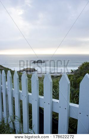 A white picket fence next to the Ocean.