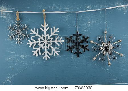 Snowflake Ornaments in Descending Height hanging from white ribbon