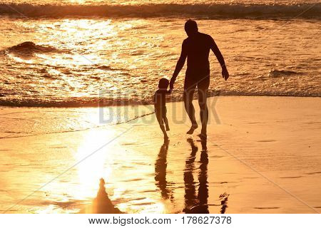Silhouette of father with son at beach in the light of the setting sun