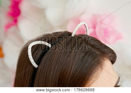 Young woman in cat ears on blurred background, closeup