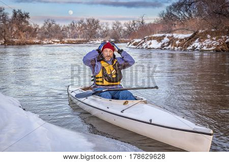 scared or concerned senior canoe paddler during winter expedition on the South Platte River in Colorado