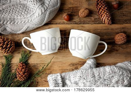 Composition of white cups, cones, knitted hat and mittens on wooden background