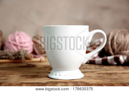 White cup and yarn balls on wooden table