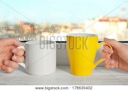 People holding cups against window