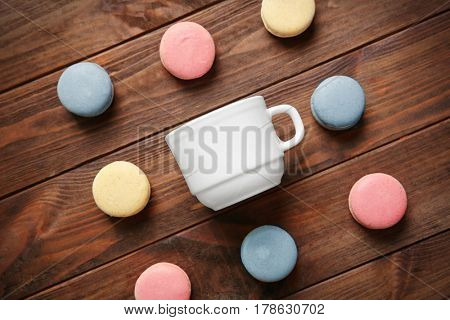 Composition of macarons and cup on wooden background