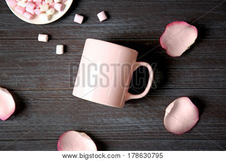 Blank cup, petals and marshmallows on grey wooden table