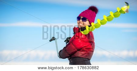 Woman, holding fishing equipment in the winter