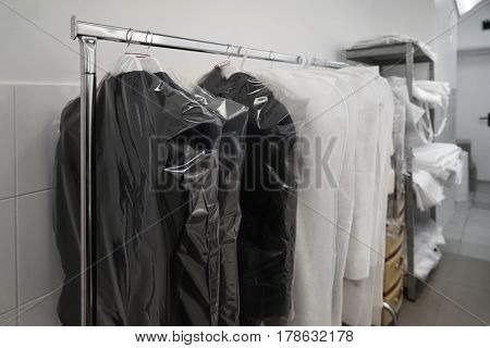 Clean packed clothes hanging in dry cleaner's workshop