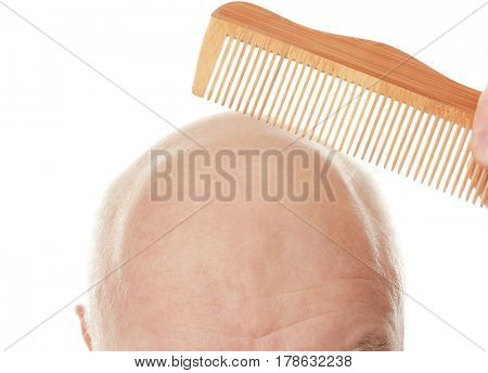 Bald senior man with comb on white background, closeup