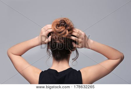 Woman with modern hairstyle on grey background