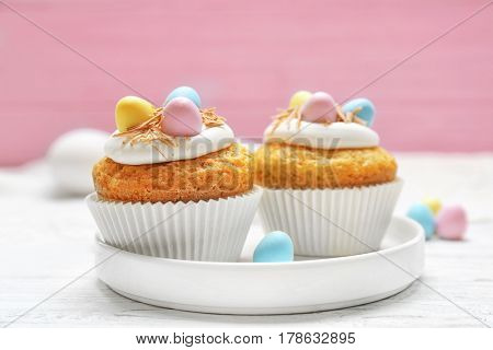 Fantastic Easter cupcakes on white wooden table and pink background