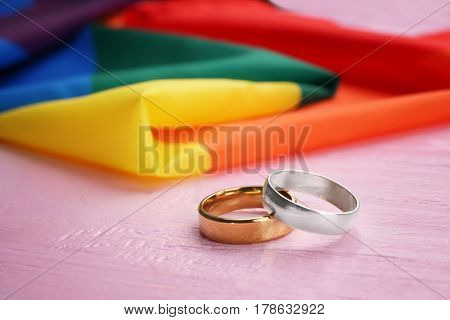 Two wedding rings and rainbow gay flag on wooden background
