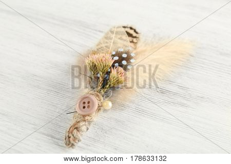 Beautiful feather boutonniere on light wooden background
