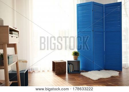 Modern interior design with furniture and blue wooden screen