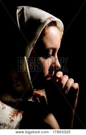 Portrait of pretty praying girl with old russian shawl on head on black background.