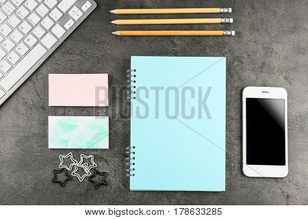 Notebook, business cards and smart phone on grunge background