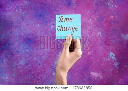 Female hand holding card with text TIME CHANGE on color background