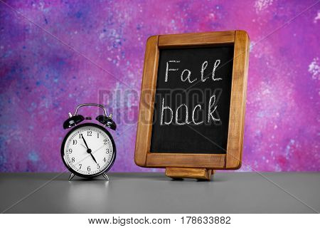 Chalkboard with text FALL BACK and retro alarm clock on table against color wall